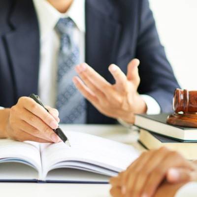 lawyer pointing to open book for client